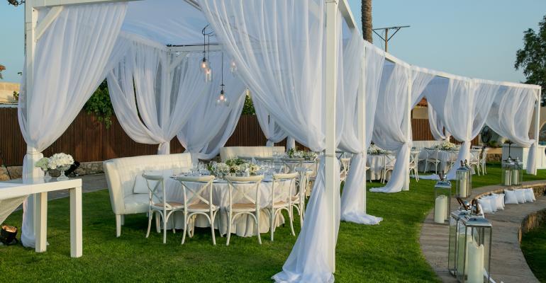 Draped dining area for seaside wedding