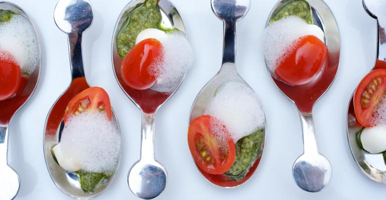 From Epicurean Caprese spoons with fresh mozzarella pear tomatoes nutfree basil pesto and white balsamic foam Photo by Laurie Smith