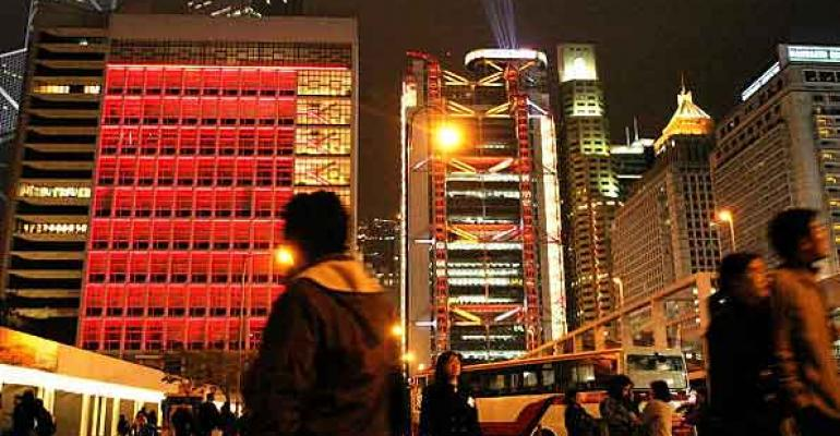 People walk past buildings on the Victoria Waterfront in Hong Kong