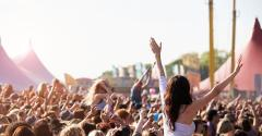 Woman at music festival with arms in air