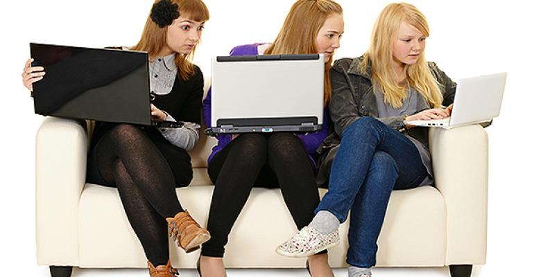 Girls looking at one anothers computers